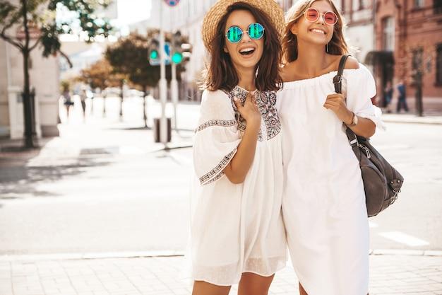 Мода портрет двух молодых стильных хиппи брюнетка и белокурые женщины в солнечный летний день. модели одеты в белую хипстерскую одежду. женщина позирует схожу с ума