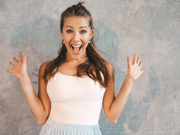 空気中の手で見ている若い美しい驚く女性。カジュアルな夏服でトレンディな女の子。灰色の壁に近いポーズの女性