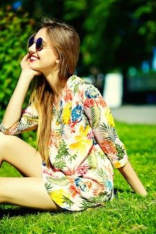 草の上に座って夏の明るい流行に敏感な布ドレスで面白いスタイリッシュなセクシーな笑顔の美しい若い女性モデル