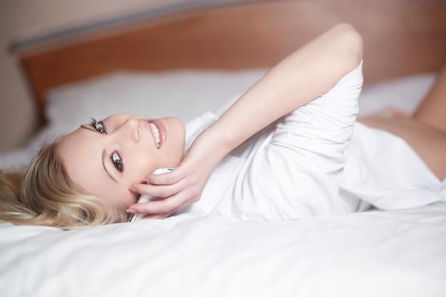 Молодая счастливая усмехаясь красивая женщина лежа на кровати и говоря на телефоне