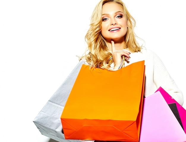 Портрет красивые милые счастливые сладкие улыбающиеся блондинка женщина держит в руках большие покупки красочные сумки в хипстерской одежде, изолированных на белом