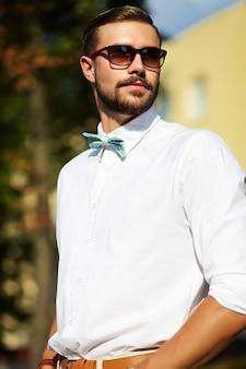 サングラスでポーズをとってスタイリッシュな夏服でハンサムな流行に敏感なモデル男