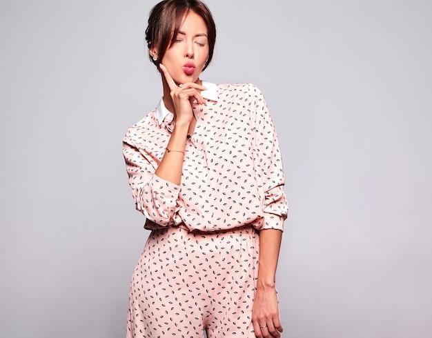 Портрет красивой милой брюнетки модель в повседневной летней одежде без макияжа, изолированные на серую стену. воздушный поцелуй