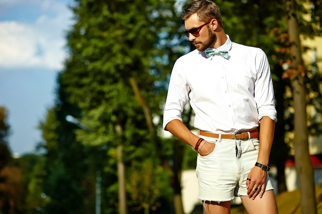 Красивый битник модель мужчина в стильной летней одежде позирует в солнцезащитные очки