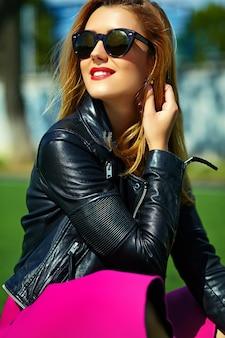 面白いクレイジーグラマースタイリッシュなセクシーな笑みを浮かべて美しい金髪の若い女性モデルの公園の芝生に座っている流行に敏感な服