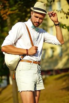 バッグと帽子でポーズをとってスタイリッシュな夏服でハンサムなヒップスターモデル男