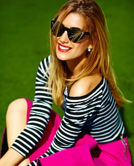 おかしいクレイジーグラマースタイリッシュなセクシーな笑みを浮かべて美しい金髪の若い女性モデル公園の芝生に座っているピンクのヒップスターの服