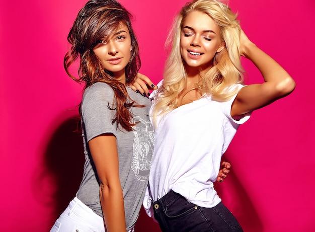 Модный портрет улыбающихся брюнеток и белокурых моделей в летней повседневной одежде на красочной розовой стене