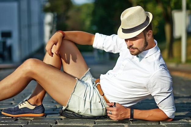 バッグと帽子に座っているスタイリッシュな夏服でハンサムなヒップスターモデル男