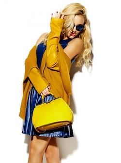 Портрет красивой счастливой сладкой улыбающейся блондинки женщины в повседневной хипстерской теплой зимней одежде свитера, с желтой сумочкой в солнцезащитных очках