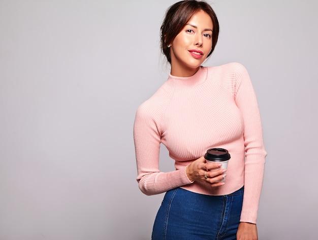 白で隔離される化粧なしのカジュアルな夏のピンクの服でかわいいブルネット美人モデルの肖像画。コーヒーを飲んでいる