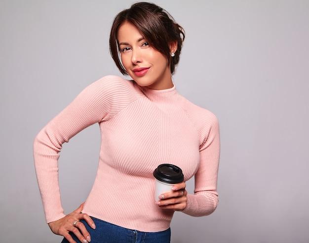 グレーに分離された化粧なしでカジュアルな夏のピンクの服でかわいいブルネット美人モデルの肖像画。コーヒーを飲んでいる