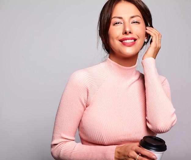 グレーに分離された化粧なしのカジュアルな夏のピンクの服で美しい笑顔かわいいブルネットの女性モデルの肖像画。コーヒーを飲んでいる