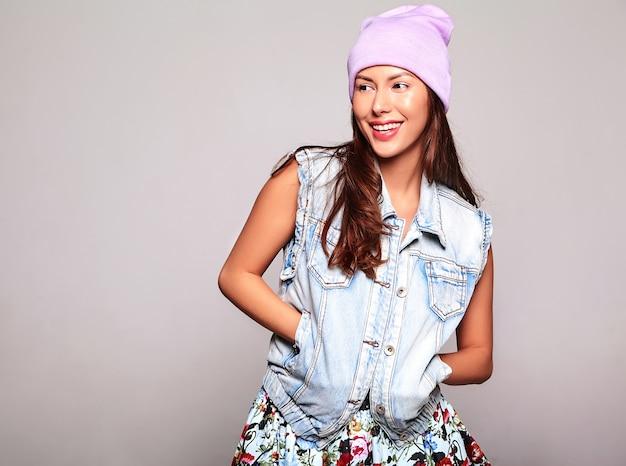 Портрет красивой улыбающейся милой модели брюнетки в повседневной джинсовой одежде без макияжа в фиолетовой шапочке, изолированной на сером