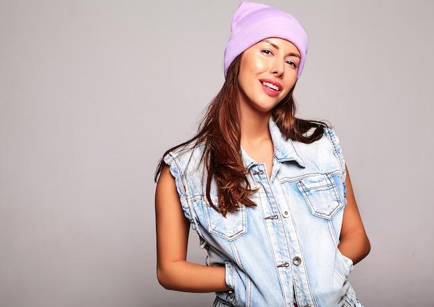 Портрет красивой милой брюнетки модели в повседневной джинсовой одежде без макияжа в фиолетовой шапочке, изолированной на сером