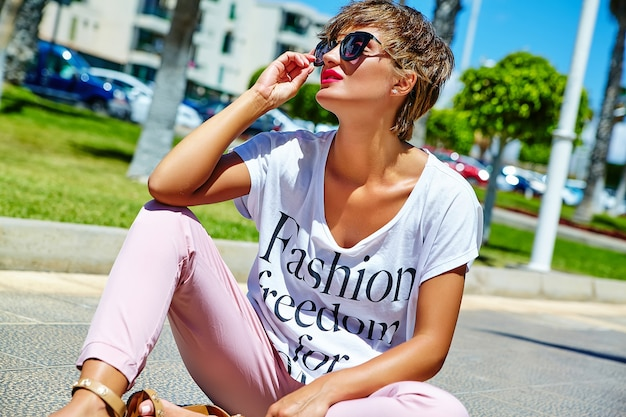 夏の流行に敏感なカジュアルな服を着てポーズとアスファルトの上に座ってファッションスタイリッシュな美しい若いブルネットの女性モデル