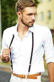 Красивый хипстер модель мужчина в стильной летней одежде позирует