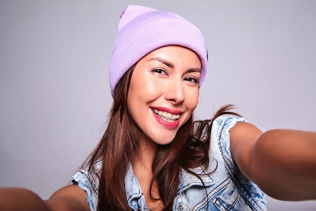 Портрет красивой улыбающейся милой брюнетки модели в повседневной джинсовой одежде без макияжа в фиолетовой шапочке, делающей селфи фото на телефон изолированную на сером