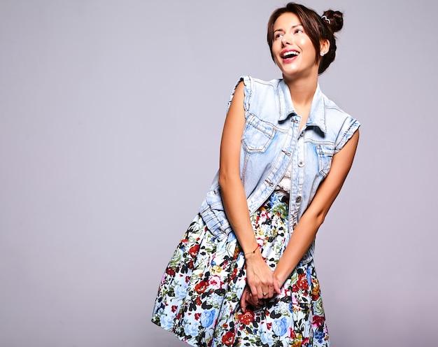 Портрет красивой улыбающейся милой модели брюнетки в повседневной джинсовой одежде без макияжа с роговой прической на сером