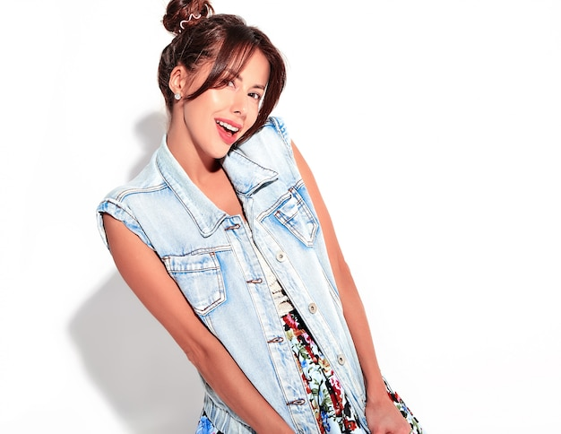 白で隔離される角髪型と化粧なしでカジュアルな夏のジーンズ服で笑顔のかわいいブルネット美人モデルの肖像画