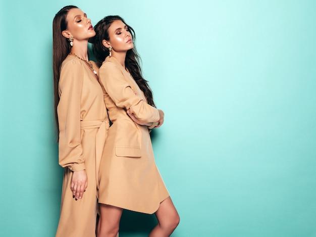 Две молодые красивые брюнетки девушки в красивой модной летней одежде. сексуальные беззаботные женщины, позирует возле голубой стены в студии