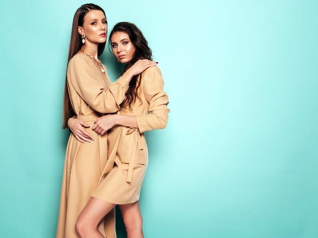 Две молодые красивые брюнетки девушки в красивых модных летних костюмах одинаковых костюмов. сексуальные беззаботные женщины позируют возле синей стены в студии