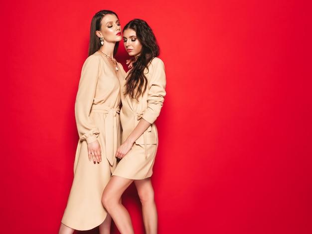 Две молодые красивые брюнетки в модных летних похожих костюмах одеваются
