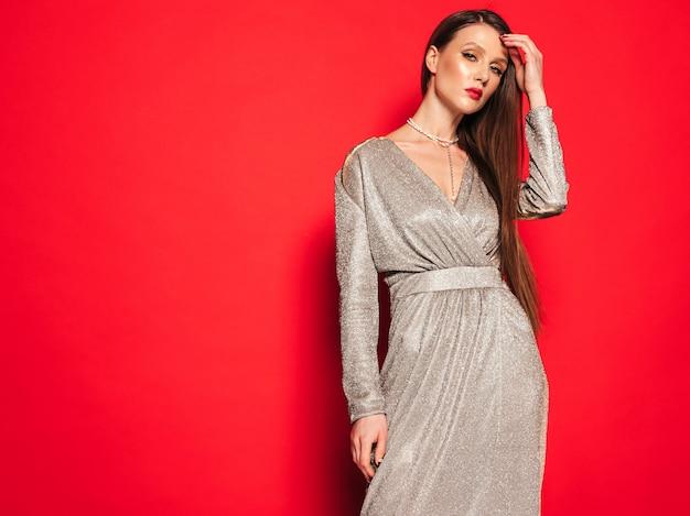 素敵なトレンディな夏のドレスの若い美しいブルネットの少女。セクシーな屈託のない女性がスタジオの赤い壁に近いポーズ。明るい夜メイクでファッショナブルなモデル