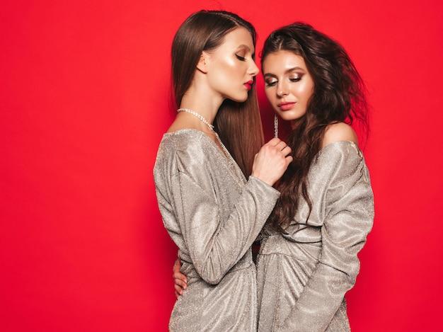 Две молодые красивые брюнетки в модном летнем блестящем платье