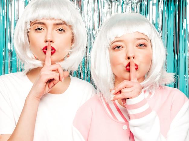 Две молодые сексуальные улыбающиеся хипстерские девушки в белых париках и красных губах. красивые женщины в летней одежде. модели позируют на серебряном блестящем фоне мишуры в студии. они показывают пальцем молчание знак молчания, жест