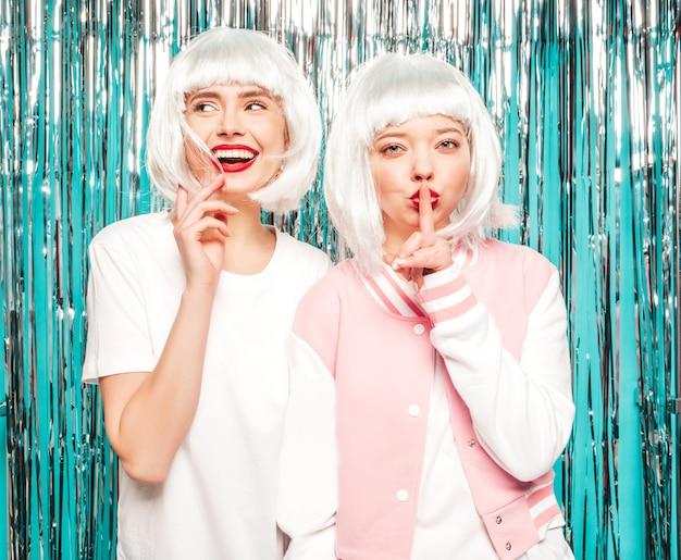Две молодые сексуальные хипстерские девушки в белых париках и красных губах. красивые модные женщины в летней одежде. модели позируют на синем серебряном блестящем фоне мишуры в студии. показывает пальцем молчание знак молчания, жест