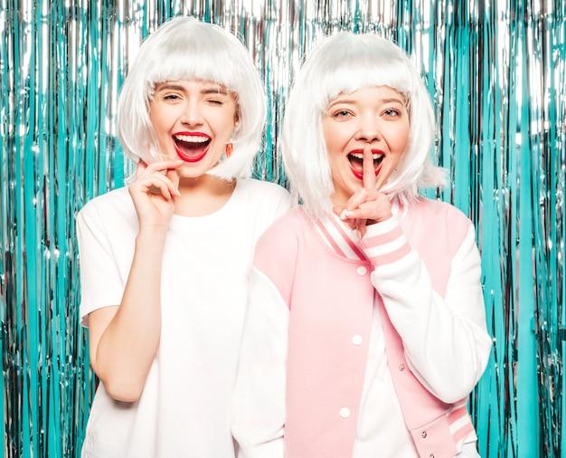 Две молодые сексуальные улыбающиеся хипстерские девушки в белых париках и красных губах. красивые женщины в летней одежде. модели позируют на серебряном блестящем фоне мишуры в студии. показывает пальцем молчание знак молчания, жест