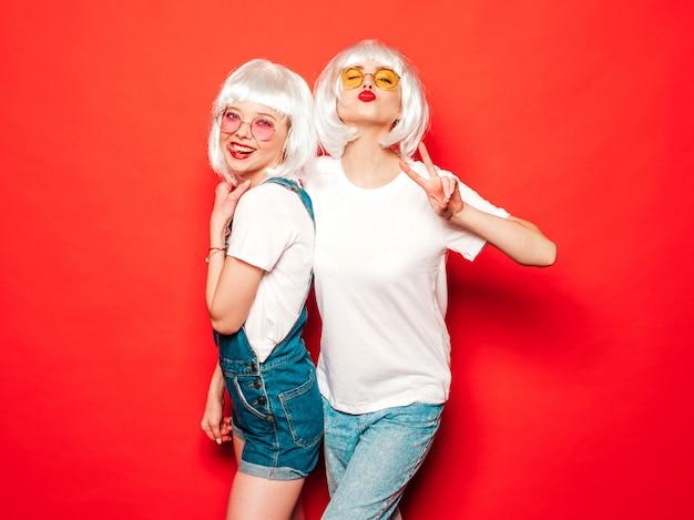 Две молодые сексуальные улыбающиеся хипстерские девушки в белых париках и красных губах. красивые модные женщины в летней одежде. беззаботные модели, позирует возле красной стены в студии летом сходит с ума