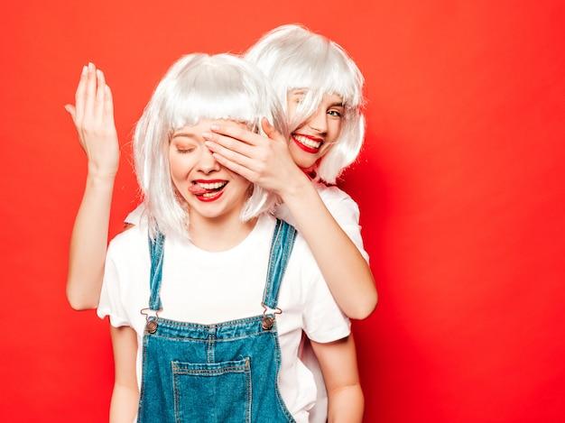 Две молодые сексуальные улыбающиеся хипстерские девушки в белых париках и красных губах. красивые модные женщины в летней одежде. модели позируют возле красной стены в студии. закройте глаза руками своей подруге. концепция сюрприз