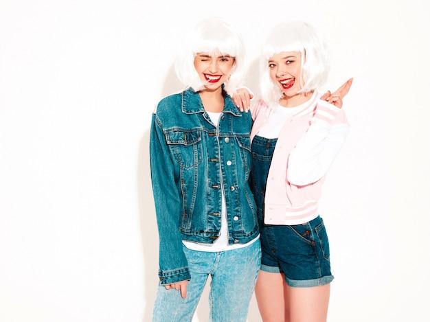 Две молодые сексуальные хипстерские девушки в белых париках и красные губы летом в солнцезащитных очках. показывает язык