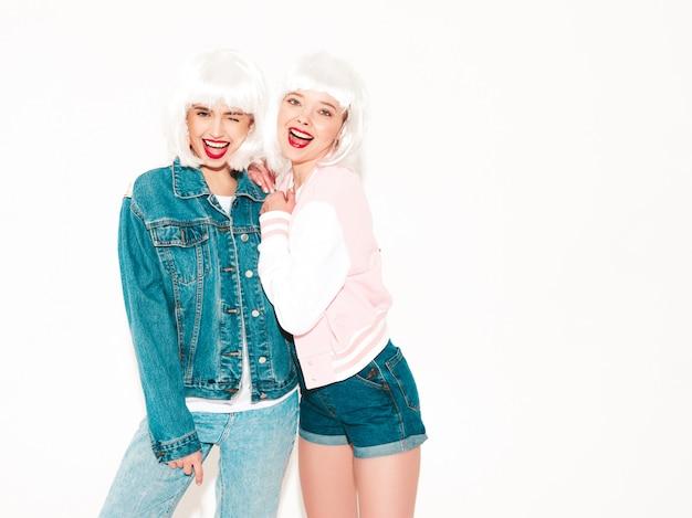 Две молодые сексуальные хипстерские девушки в белых париках и красные губы летом в солнцезащитных очках