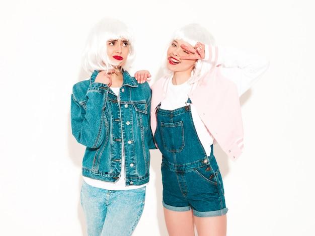 Две молодые сексуальные хипстерские девушки в белых париках и красные губы в солнечных очках. показывает язык