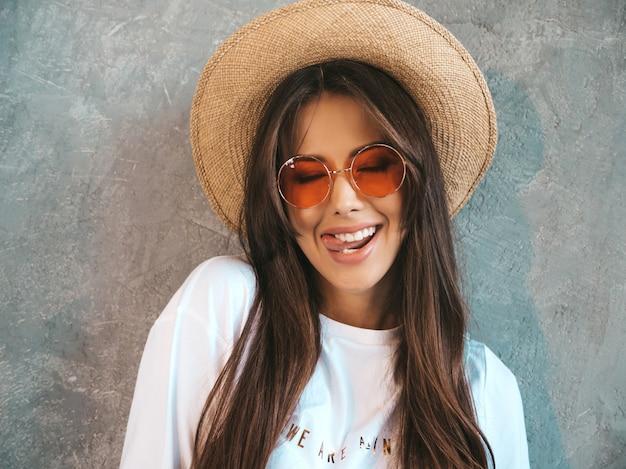 Молодая красивая улыбается женщина ищет. модная девушка в повседневной летней футболке с одеждой и шляпой .. показывает язык