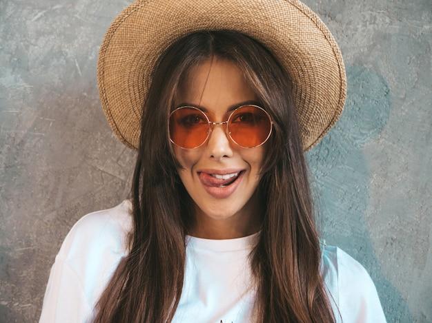 探している若い美しい笑顔の女性のポートレート、クローズアップ。カジュアルな夏服と帽子でトレンディな女の子。面白い顔を作ると舌を見せて肯定的な女性