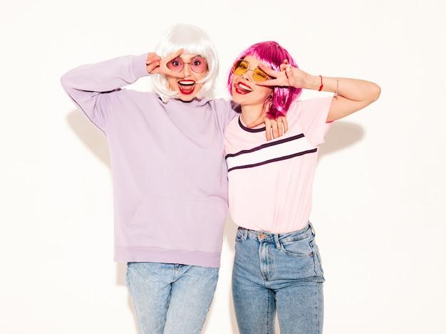 Две молодые сексуальные улыбающиеся хипстерские девушки в париках и красных губах. красивые модные женщины в летней одежде. беззаботные модели, позирует возле белой стены в студии показывает знак мира