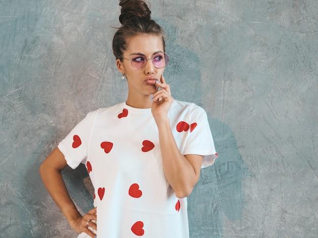探している若い美しい女性。カジュアルな夏の白いドレスとサングラスでトレンディな女の子。 。考え