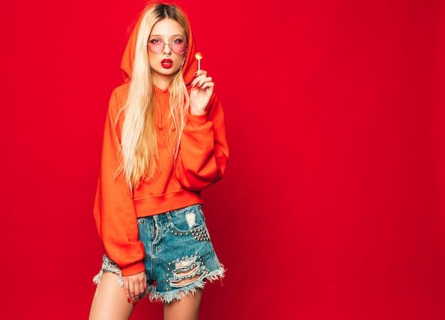 Портрет молодой красивой битник плохая девушка в модном красном балахоне и серьги в носу. позитивная модель лижет круглые леденцы
