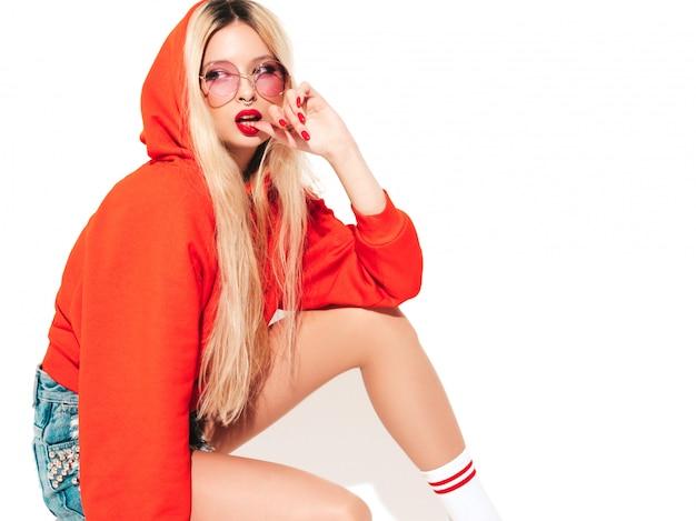 トレンディな赤いパーカーと彼女の鼻にイヤリングの若い美しい流行に敏感な悪い女の子の肖像画。スタジオに座っているセクシーな屈託のない笑顔の金髪女性。楽しい肯定的なモデル。白で隔離