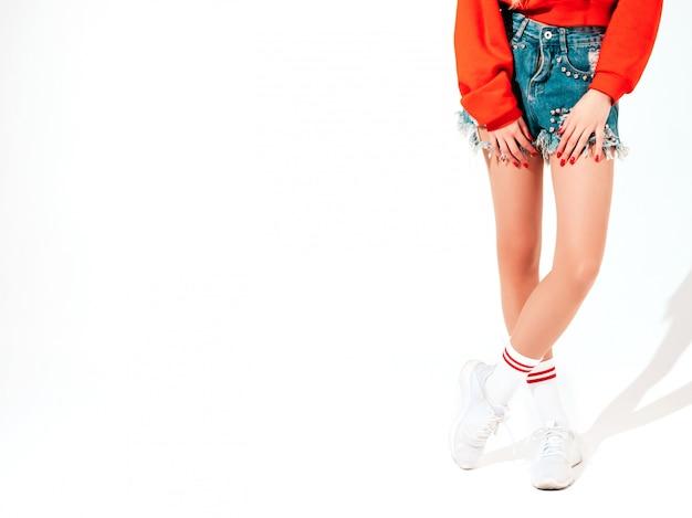 トレンディな赤いパーカーと彼女の鼻にイヤリングの若い美しい流行に敏感な悪い女の子の肖像画。楽しい肯定的なモデル。白で隔離