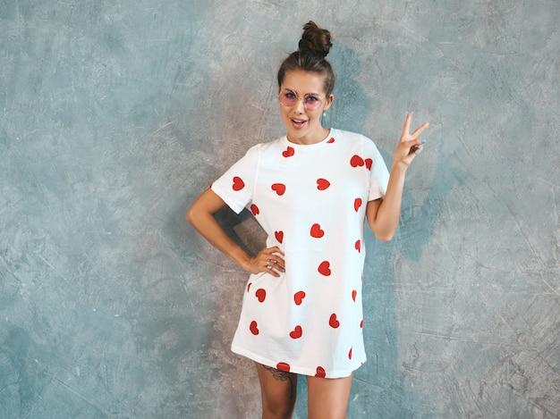 探している若い美しい笑顔の女性。カジュアルな夏の白いドレスとサングラスでトレンディな女の子。