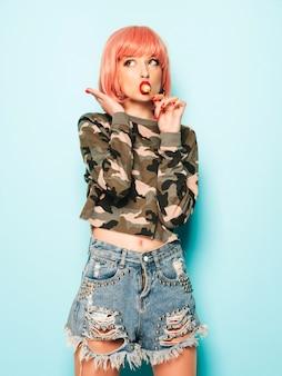 トレンディなジーンズのショートパンツと彼女の鼻にイヤリングの若い美しい流行に敏感な悪い女の子の肖像画。丸い砂糖菓子を舐めている肯定的なモデル