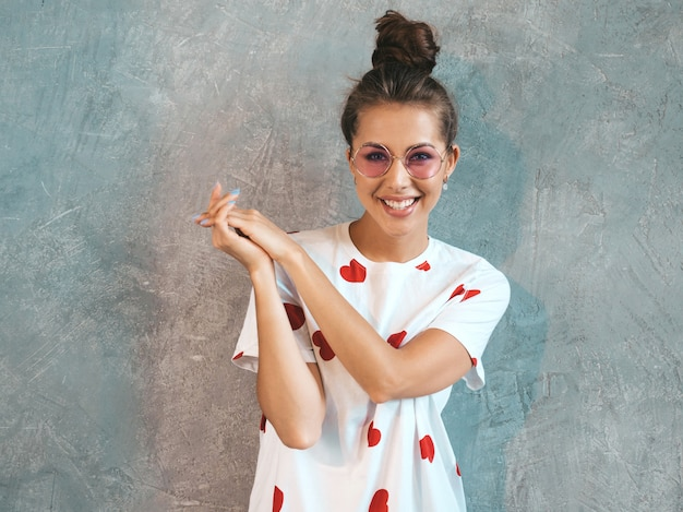 探している若い美しい笑顔の女性の肖像画。カジュアルな夏の白いドレスとサングラスでトレンディな女の子。