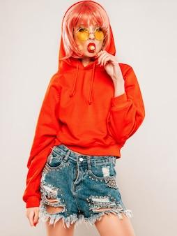 トレンディな赤い夏赤いパーカーと彼女の鼻にイヤリングの若い美しい流行に敏感な悪い女の子。セクシーな屈託のない女性がかつらの灰色の背景のスタジオでポーズします。丸い砂糖菓子を舐めるホットモデル