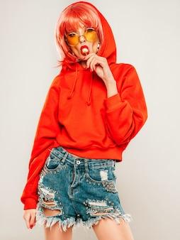 トレンディな赤い夏のパーカーと彼女の鼻にピアスの若い美しい流行に敏感な悪い女の子の肖像画。かつらのスタジオでポーズをとってセクシーな屈託のない笑顔の金髪女性。丸い砂糖菓子を舐めている肯定的なモデル