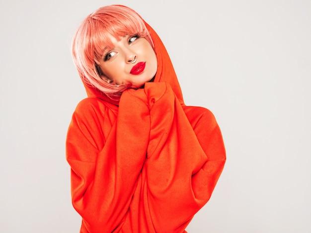 トレンディな赤い夏のパーカーと彼女の鼻にピアスの若い美しい流行に敏感な悪い女の子。灰色の背景のスタジオでポーズをとってピンクのかつらのセクシーな屈託のない女性。
